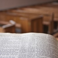 A bible in a church pulpit overlooking the church